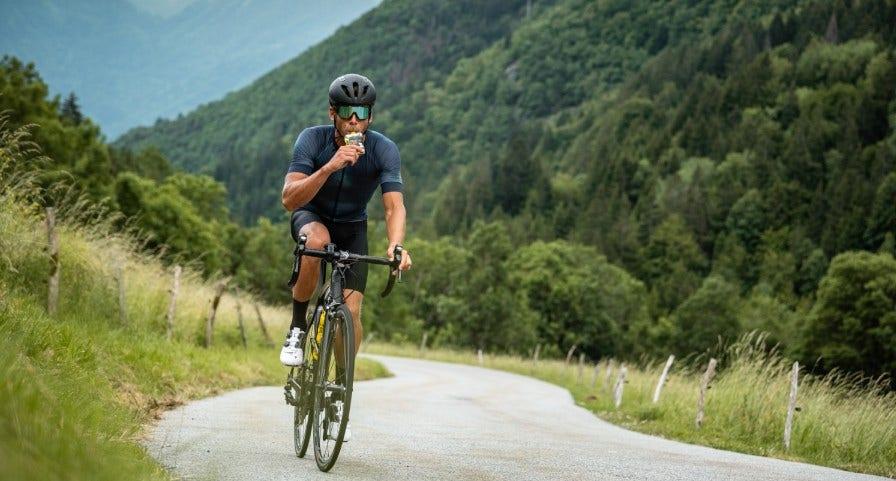 Cycliste en train de prendre un gel énergétique Isostar pendant son entrainement
