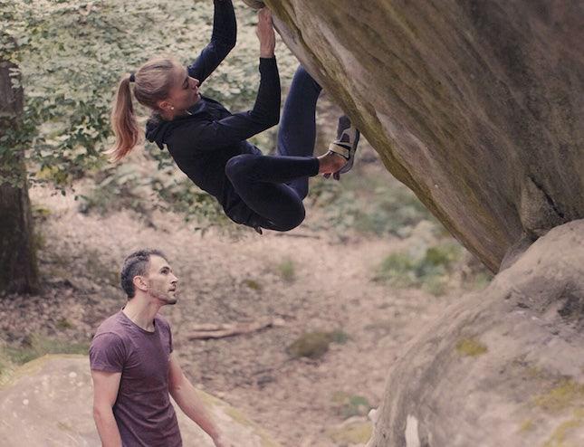 Manu Cornu en train de guider une femme lors d'une séance d'escalade en extérieur